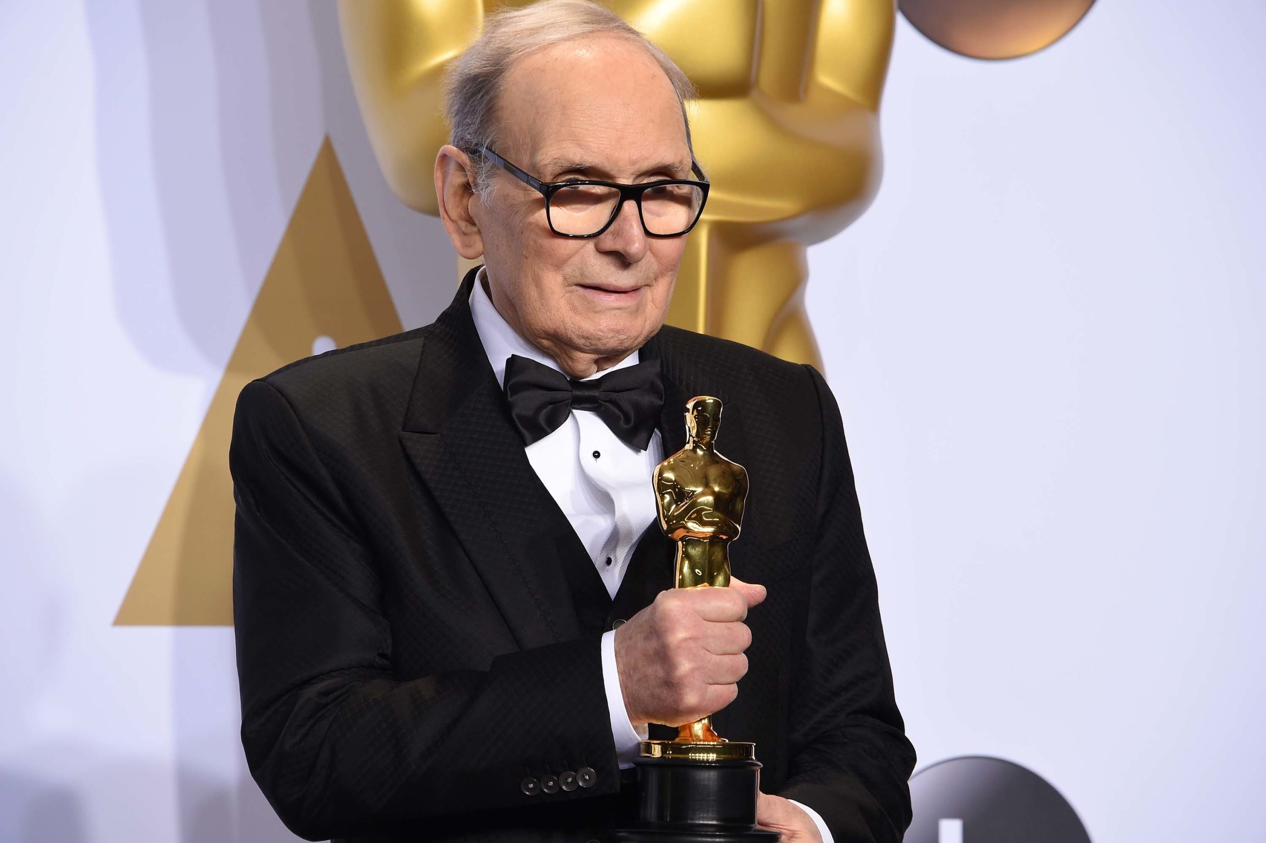 """Composer Ennio Morricone poses with the Oscar for Best Original Score, """"The Hateful Eight,"""" in the press room during the 88th Oscars in Hollywood on February 28, 2016. (Photo by Robyn BECK / AFP) (Photo by ROBYN BECK/AFP via Getty Images)"""